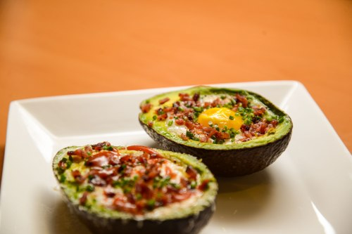 Eggs on Avocado with bacon, reggiano parmigiano and sirracha.