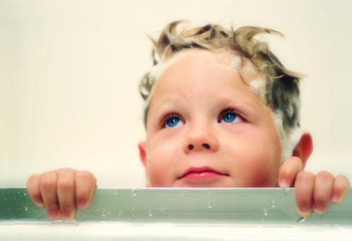 Happy four year old boy taking a bath.